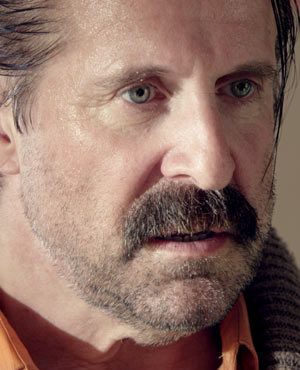 Mr. Olivetti played by Peter Stormare in Small Apartments