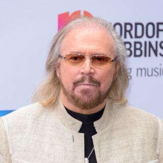 Barry Gibb receives his knighthood from Prince Charles