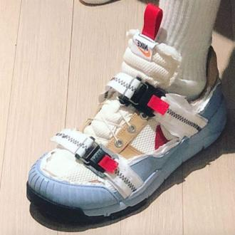 Frank Ocean modifies a pair of  Tom Sachs Nike trainers
