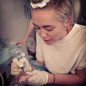 Miley Cyrus Gives Tattoo