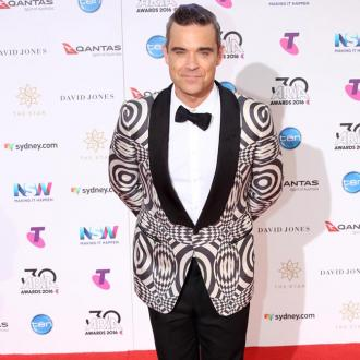 Robbie Williams gives away BRIT Award trophies to pals